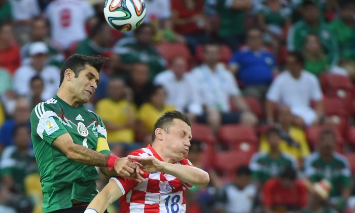 Croatia's forward Ivica Olic (R) and Mexico's defender Rafael Marquez vie for the ball during a Group A football match between Croatia and Mexico at the Pernambuco Arena in Recife during the 2014 FIFA World Cup on June 23, 2014. (EMMANUEL DUNAND/AFP/Getty Images)