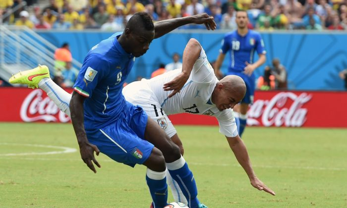 Italy's forward Mario Balotelli (L) vies with Uruguay's midfielder Egidio Arevalo Rios during a Group D football match between Italy and Uruguay at the Dunas Arena in Natal during the 2014 FIFA World Cup on June 24, 2014. (JAVIER SORIANO/AFP/Getty Images)