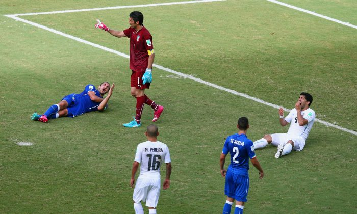 Luis Suarez of Uruguay and Giorgio Chiellini of Italy react after a clash during the 2014 FIFA World Cup Brazil Group D match between Italy and Uruguay at Estadio das Dunas on June 24, 2014 in Natal, Brazil. (Julian Finney/Getty Images)