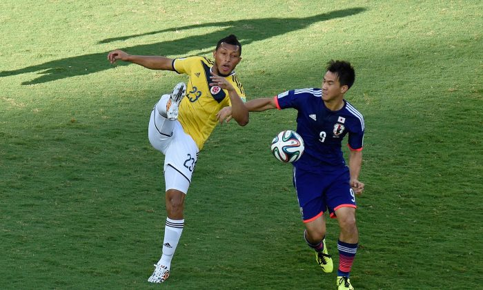 Japan's forward Shinji Okazaki (R) vies with Colombia's defender Carlos Valdes during a Group C football match between Japan and Colombia at the Pantanal Arena in Cuiaba during the 2014 FIFA World Cup on June 24, 2014. (JUAN BARRETO/AFP/Getty Images)