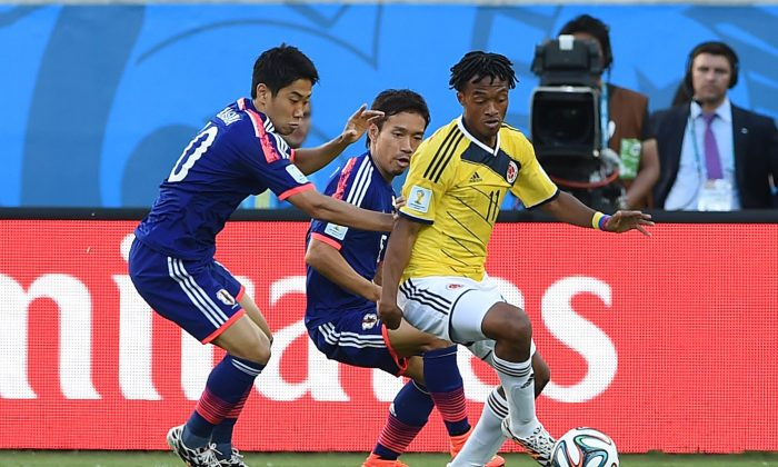 Japan's forward Shinji Kagawa (L) and Japan's defender Yuto Nagatomo (R) vie for the ball against Colombia's midfielder Juan Guillermo Cuadrado during a Group C football match between Japan and Colombia at the Pantanal Arena in Cuiaba during the 2014 FIFA World Cup on June 24, 2014. (TOSHIFUMI KITAMURA/AFP/Getty Images)