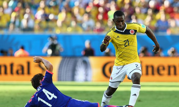 Toshihiro Aoyama of Japan tackles Jackson Martinez of Colombia during the 2014 FIFA World Cup Brazil Group C match between Japan and Colombia at Arena Pantanal on June 24, 2014 in Cuiaba, Brazil. (Elsa/Getty Images)