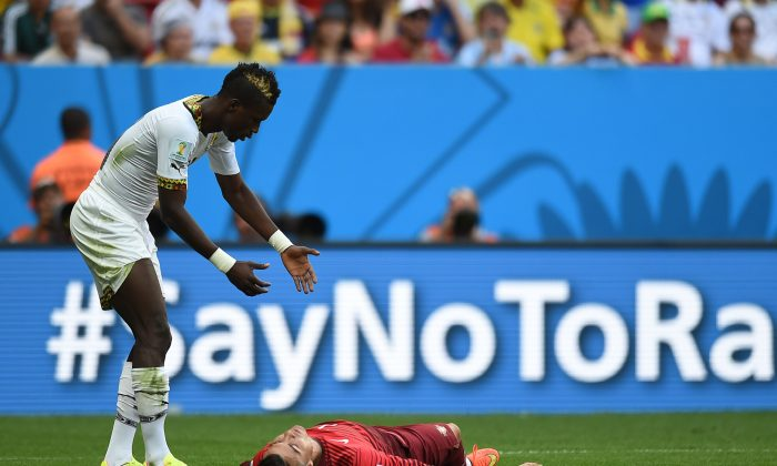 Ghana's defender John Boye (L) reacts as Portugal's forward and captain Cristiano Ronaldo lies on the ground during to the Group G football match between Portugal and Ghana at the Mane Garrincha National Stadium in Brasilia during the 2014 FIFA World Cup on June 26, 2014. (CARL DE SOUZA/AFP/Getty Images)