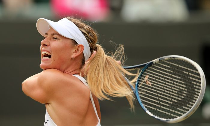 Russia's Maria Sharapova returns to Switzerland's Timea Bacsinszky during their women's singles second round match on day four of the 2014 Wimbledon Championships at The All England Tennis Club in Wimbledon, southwest London, on June 26, 2014. (ANDREW YATES/AFP/Getty Images)