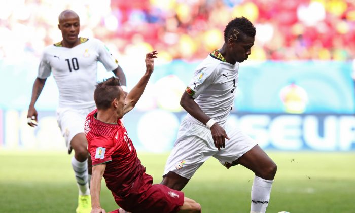 Joao Pereira of Portugal challenges Asamoah Gyan of Ghana during the 2014 FIFA World Cup Brazil Group G match between Portugal and Ghana at Estadio Nacional on June 26, 2014 in Brasilia, Brazil. (Adam Pretty/Getty Images)