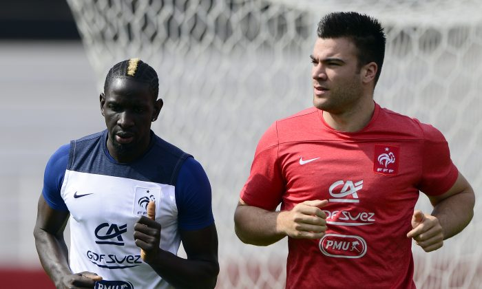 France's defender Mamadou Sakho (L) runs with a staff member during a training session at the stadium Santa Cruz in Ribeirao Preto on June 28, 2014, during the 2014 FIFA World Cup in Brazil. (FRANCK FIFE/AFP/Getty Images)