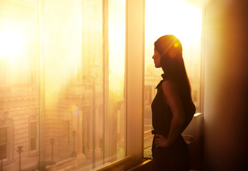 Business woman overlooking over the city at sunrise. (Getty)