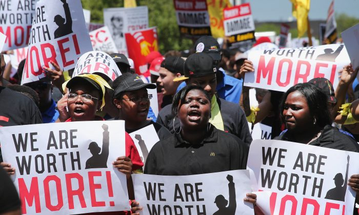 Fast food workers and activists demonstrate outside the McDonald's corporate campus Oak Brook, Illinois, in this file photo. The demonstrators were calling on McDonald's to pay a minimum wage of $15-per-hour, however, the minimum wage has many bad unintended consequences. (Scott Olson/Getty Images)