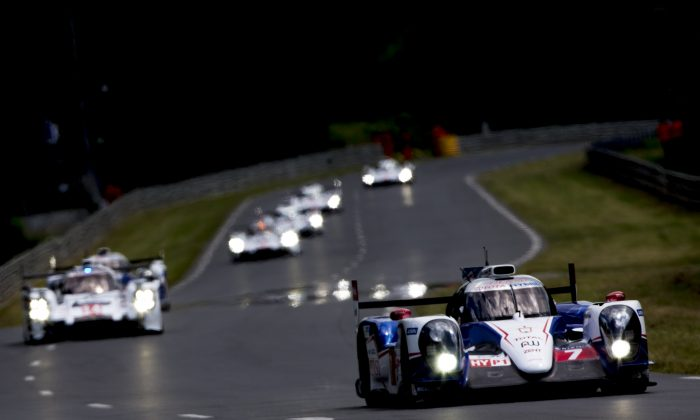 The #7 Toyota TS 040 Hybrid leads the #20 Porsche 919 Hybrid and the rest of the field during the Le Mans 24h Race on June 14, 2014 in Le Mans, France. (Andrew Hone/Getty Images)