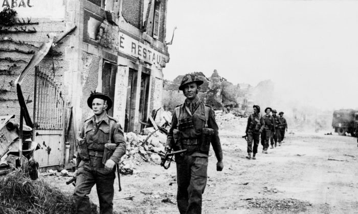 Allied soldiers cross 08 June 1944 the village of Douet, after the town of Bayeux fell, two days after the allied troops landed on Normandy beaches (north-west of France), to come as reinforcements during the historic D-Day, 06 June 1944, during WWII. (STF/AFP/Getty Images)