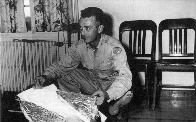 Major Jesse Marcel holds up pieces of a crashed weather balloon found 75 miles northwest of Roswell, N.M., in June 1947. Purported leaked documents, known as the Majestic 12 documents, claim that the weather balloon was a cover story for an extraterrestrial crash. If the documents are genuine, then a highly secret agency known as the Majestic 12 may have overseen the cleanup and cover-up of said crash. (United States Air Force/AFP/Getty Images)