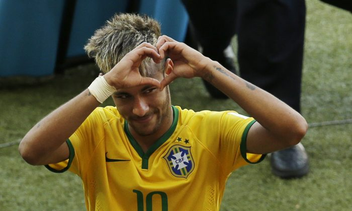 Brazil's Neymar forms a heart with his hands as he leaves the pitch after the World Cup round of 16 soccer match between Brazil and Chile at the Mineirao Stadium in Belo Horizonte, Brazil, Saturday, June 28, 2014. Brazil won 3-2 on penalties after the match ended 1-1 draw after extra-time. (AP Photo/Hassan Ammar)