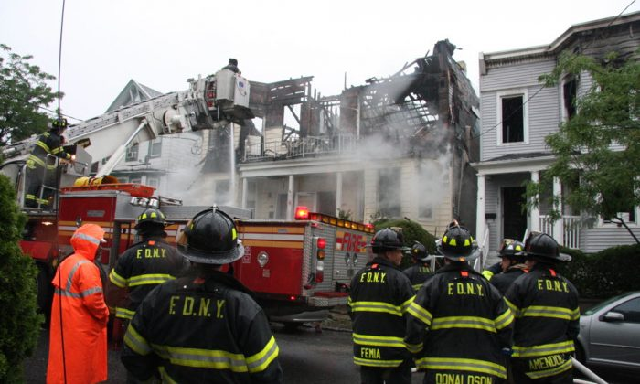 Firefighters continue working the scene of a fire that tore through three townhouses on New York City's Staten Island, on June 5, 2014.(AP Photo/Staten Island Advance, Irving Silverstein)