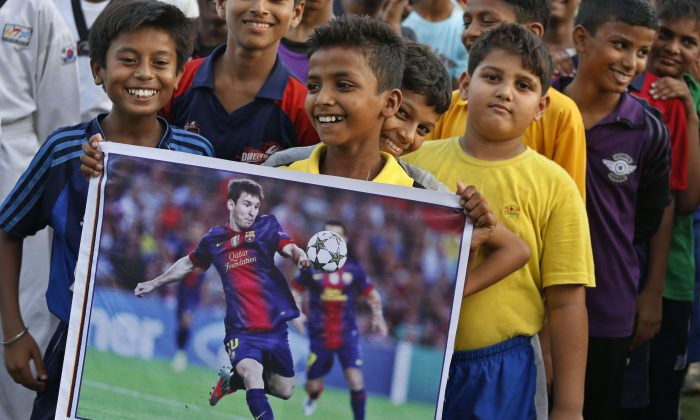 An Indian boy holds a poster of Argentina's Lionel Messi as sports enthusiasts gather at an event to celebrate the Soccer World Cup in Allahabad, India, Thursday, June 12, 2014. Nearly half the world's population, well over 3 billion spectators, is expected to watch soccer's premier event that kicks off in Brazil Thursday. (AP Photo/ Rajesh Kumar Singh)