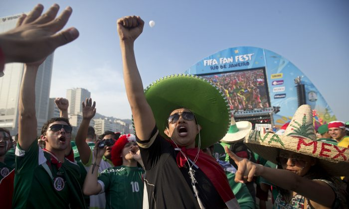 A Mexico soccer fan cheers before his team's World Cup match with Brazil inside the FIFA Fan Fest area on Copacabana beach in Rio de Janeiro, Brazil, Tuesday, June 17, 2014. Telemundo will broadcast the 2018 and 2022 World Cups, taking over from Univision. (AP Photo/Silvia Izquierdo)