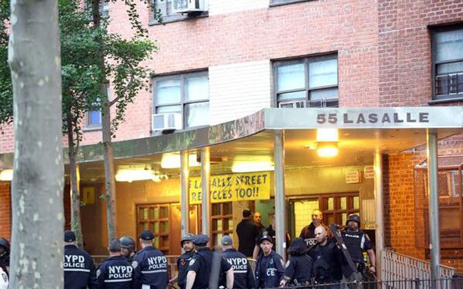Police officers stand outside a housing project during an early morning raid in West Harlem on Wednesday. (Courtesy of NYPD)