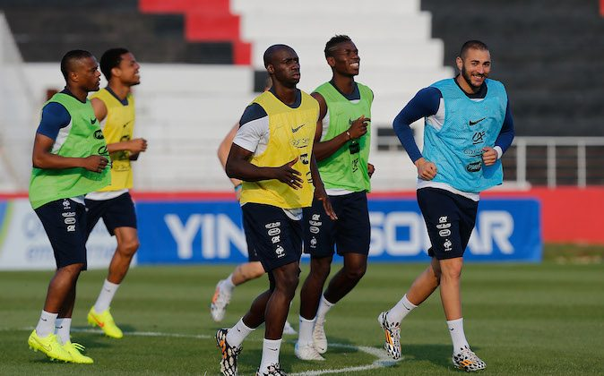 France's Paul Pogba, green shirt, center, smiles with Karim Benzema, blue shirt, as they run in the field during a training session of the French national soccer team at the Santa Cruz Stadium in Ribeirao Preto, Brazil, Wednesday, June 11, 2014. France will face Ecuador, Switzerland and Honduras in group E of the 2014 Soccer World Cup. (AP Photo/David Vincent)