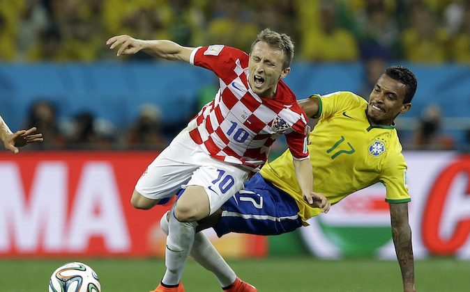 Croatia's Luka Modric is fouled by Brazil's Luiz Gustavo, right, during the group A World Cup soccer match between Brazil and Croatia, the opening game of the tournament, in the Itaquerao Stadium in Sao Paulo, Brazil, Thursday, June 12, 2014.  (AP Photo/Kirsty Wigglesworth)
