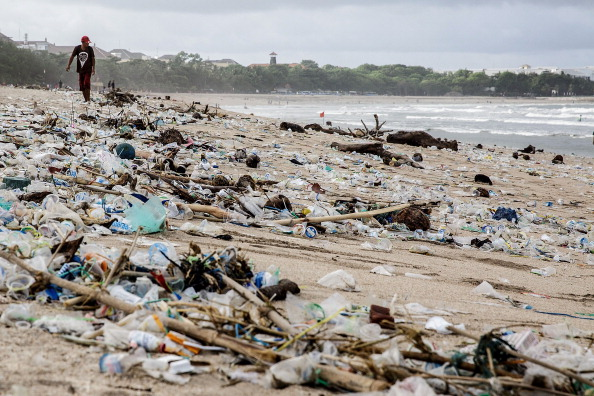 A man walks beside the scattered plastic trash brought in by strong waves at Kuta Beach on January 17, 2014 in Kuta, Indonesia. (Agung Parameswara/Getty Images)