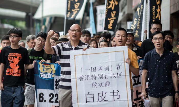 Demonstrators shout slogans, holding a large reproduction of Beijing's white paper, as they march toward Beijing's representative office in Hong Kong on June 11. China released a white paper document Tuesday emphasizing its control over Hong Kong. (Philippe Lopez/AFP/Getty Images)