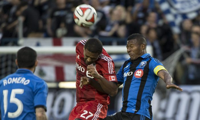 Toronto FC's Luke Moore heads the ball away from Montreal Impact's Patrice Bernier during first half Voyageurs Cup action on June 4, 2014 in Montreal. (The Canadian Press/Paul Chiasson)