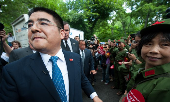Chen Guangbiao, a Chinese businessman, stands outside the Loeb Boathouse with his security entourage on June 25. Chen organized a confusing event, ostensibly for homeless New Yorkers, in which he vilified a Chinese spiritual practice. (Dai Bing/Epoch Times)