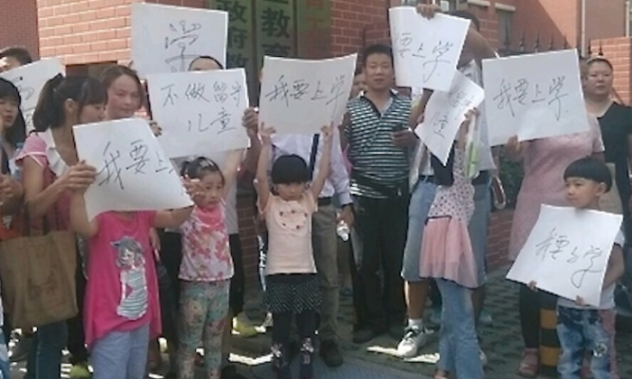 Migrant worker parents and children protest in front of Beijing's suburban Chaoyang district education department on May 25, 2014. Their children have been barred from attending school in Beijing because they do not have the needed residency papers. (Photograph supplied)