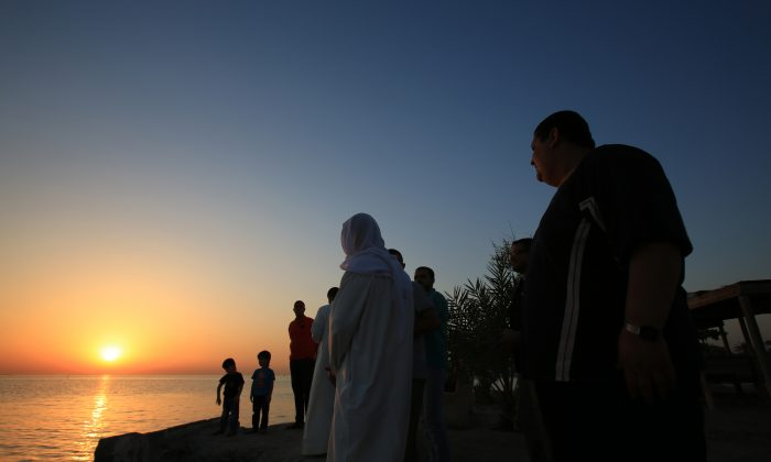 Bahrainis look for the sliver of a new moon that would indicate the start of the Islamic holy month of Ramadan, while standing on the shore of the Persian Gulf in the western village of Karzakan, Bahrain, Saturday, June 28, 2014. Ramadan, for observant Muslims, is a time of fasting, prayer and charitable giving. Bahraini officials announced Ramadan would begin Sunday. (AP Photo/Hasan Jamali)