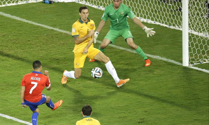 Chile's Alexis Sanchez, left, scores his team's first goal during the group B World Cup soccer match between Chile and Australia in the Arena Pantanal in Cuiaba, Brazil, Friday, June 13, 2014. (AP Photo/Michael Sohn)