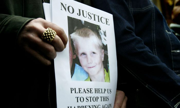 Relatives of nine-year-old Callum Oakford, killed by a hit-and-run driver, hold a poster bearing his image at Chichester Crown Court on February 12th, 2004. New Public Health reports are calling for local authorities to improve child accident protection strategies. (Ian Waldie/Getty Images)