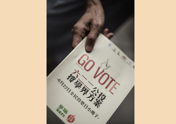 An activist distributes leaflets asking residents of Hong Kong to cast ballots for a June 22 referendum concerning universal suffrage, on June 12, 2014. A white paper on Hong Kong issued by the Chinese regime appears to have aroused people's interest in the referendum while simultaneously alienating the people of Taiwan. (Philippe Lopez/AFP/Getty Images)