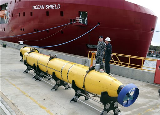 """In this March 30, 2014 file photo, an autonomous underwater vehicle (AUV) sits on the wharf at naval base HMAS Stirling in Perth, Australia, ready to be fitted to the Australian warship Ocean Shield to aid in the search for the missing Malaysia Airlines Flight 370. In an interview with The Associated Press, Martin Dolan, chief commissioner of the Australian Transport Safety Bureau, said that he was """"cautiously optimistic"""" that the lost jet would be found. Dolan said he was confident the airliner was close to a 700-kilometer by 80-kilometer arc of ocean identified from satellite data that investigators would be scouring in the next phase of the search. (AP Photo/Rob Griffith, File)"""