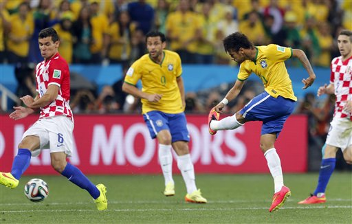 Brazil's Neymar, left, shoots to score past Croatia's Dejan Lovren, left, as Brazil's Fred, center, watches during the group A World Cup soccer match in the opening game of the tournament at Itaquerao Stadium in Sao Paulo, Brazil, Thursday, June 12, 2014. (AP Photo/Frank Augstein)