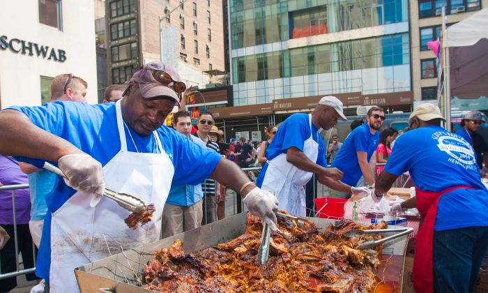 The hog is pulled apart and doused with sauce. (Rob Counts/Epoch Times)