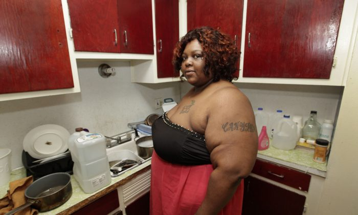 Detroit resident Nicole Hill stands in her kitchen on June 25, 2014. Hill, who owes the Detroit water department almost $6000, has been washing her dishes with bottled water since her water was shut off. To call attention to the Detroit water shutoffs, the Council of Canadians is bringing 1,000 litres of water to the city on July 24. (AP Photo/Paul Sancya)
