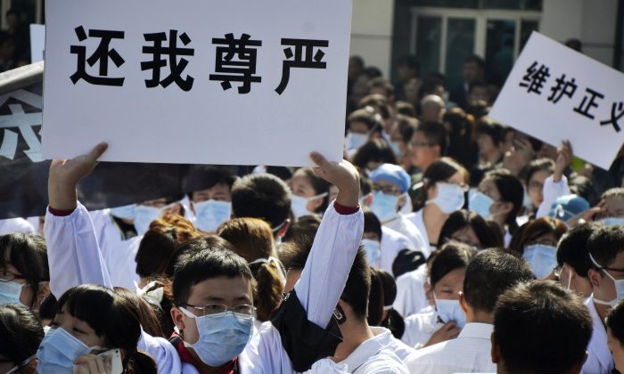 Hospital workers hold banners as they protest against attacks on medical workers outside the No. 1 People's Hospital in Wenling, east China's Zhejiang province, on Oct. 28, 2013. The relationship between patients and hospitals has often been characterized by mistrust, and sometimes outright violence. (Jin Yunguo/AFP/Getty Images)