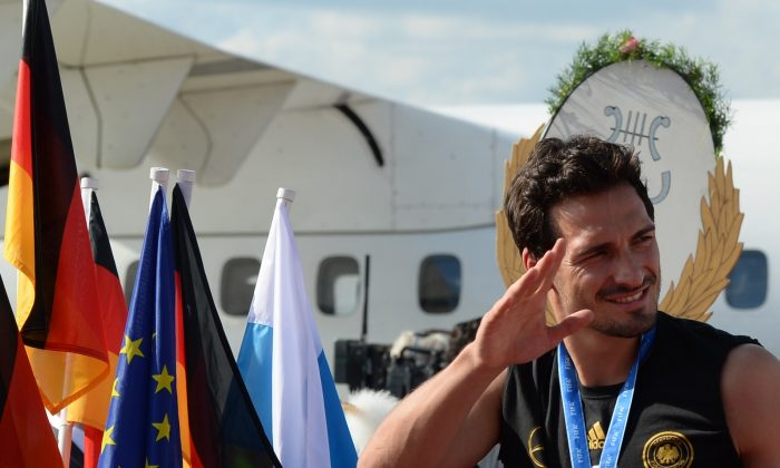 German national football team player Mats Hummels waves after disembarking an airplane at the airport in Munich, southern Germany, on July 15, 2014. After attending a victory parade in Berlin, the Bayern Munich players of the national team and other players living in the South of the country took a plane to Munich, where they were expected by thousands of football fans celebrating the 2014 FIFA Football World Cup title. (CHRISTOF STACHE/AFP/Getty Images)