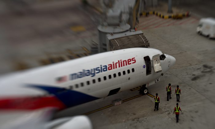 In this picture taken with a Tilt and shift lens, groundstaff walk past a Malaysia Airlines plane parked on the tarmac at the Kuala Lumpur International Airport in Sepang. (Manan Vatsyanyana/AFP/Getty Images)