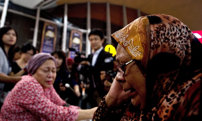 "Relatives of people onboard Malaysia Airlines flight MH17 from Amsterdam react outside the family holding area at the Kuala Lumpur International Airport in Sepang on July 18, 2014. A Malaysian airliner carrying 295 people from Amsterdam to Kuala Lumpur crashed on July 17 in rebel-held east Ukraine, as Kiev said the jet was shot down in a ""terrorist"" attack. Ukraine's government and pro-Russian insurgents traded blame for the disaster, with comments attributed to a rebel commander suggesting his men may have downed Malaysia Airlines flight MH17 by mistake, believing it was a Ukrainian army transport plane. (MANAN VATSYAYANA/AFP/Getty Images)"