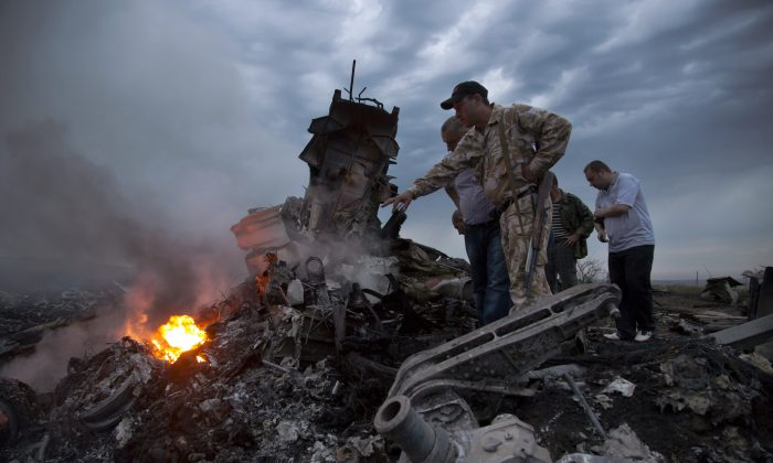 People inspect the crash site of a passenger plane near the village of Grabovo, Ukraine, Thursday, July 17, 2014. (AP Photo/Dmitry Lovetsky)