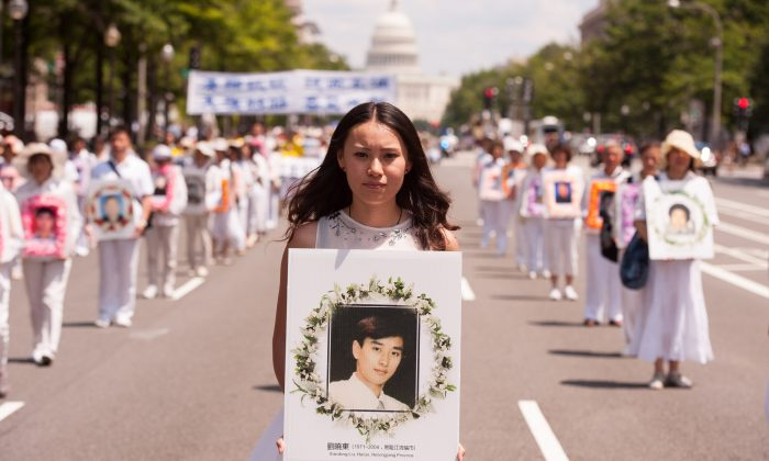 A young women holds a portrait of Falun Gong practitioner who was killed in the persecution in China, during a parade in Washington, on July 17, 2014. (Dai Bing/Epoch Times)