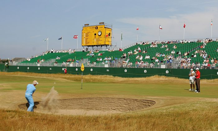 Simon Dyson (L) hits out of a greenside bunker on the 18th hole during the second round of The Open Championship at Royal Liverpool Golf Club in this July 21, 2006 photo. (Ross Kinnaird/Getty Images)