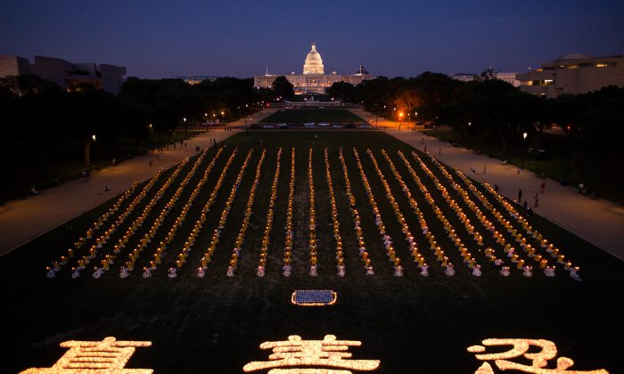Falun Gong practitioners gather together to hold a candle light vigil in front of the U.S. Capitol, to commemorate the lives lost by the persecution, in Washington, D.C., on July 17, 2014. This year marks the 15 year of the persecution that started on July 20, 1999 in China. (Dai Bing/Epoch Times)