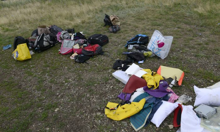 Passengers' belongings lie at the site of the crash of a Malaysia Airlines plane carrying 298 people from Amsterdam to Kuala Lumpur in Grabove, in rebel-held east Ukraine, on July 19, 2014. Ukraine and pro-Russian insurgents agreed on July 19 to set up a security zone around the crash site of a Malaysian jet whose downing in the rebel-held east has drawn global condemnation of the Kremlin. Outraged world leaders have demanded Russia's immediate cooperation in a prompt and independent probe into the shooting down on July 17 of flight MH17 with 298 people on board. (Alexander KHUDOTEPLY/AFP/Getty Images)