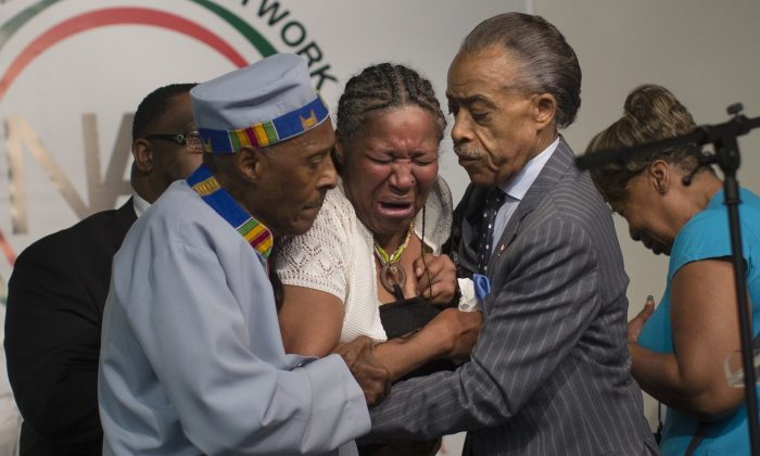Esaw Garner, wife of Eric Garner, breaks down in the arms of Rev. Herbert Daughtry (L) and Rev. Al Sharpton during a rally at the National Action Network headquarters for Eric Garner on Saturday, July 19, 2014. (AP Photo/John Minchillo)