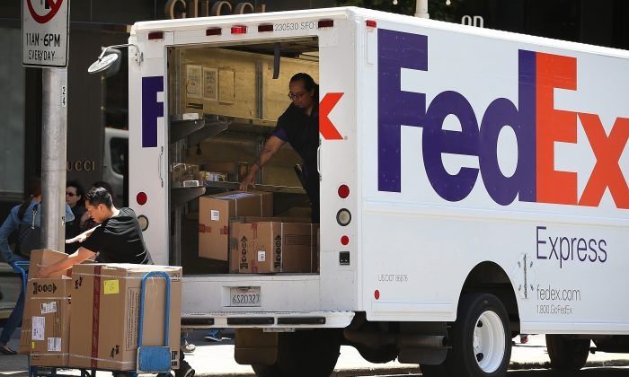 FedEx workers unload packages from a delivery truck in San Francisco, Calif., on June 19, 2013. (Justin Sullivan/Getty)