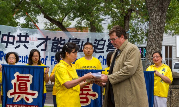 Dr. Minnan Liu (L) of the Falun Dafa Association of Edmonton presents over 4,000 signatures from Edmontonians on a petition to Brent Rathgeber, MP for Edmonton-St. Albert, on July 19, 2014 at the Dr. Wilbert McIntyre Park in Edmonton. The petition asks the Canadian government to urge the Chinese regime to stop the persecution of Falun Dafa in China. (Frank Liang/Epoch Times)