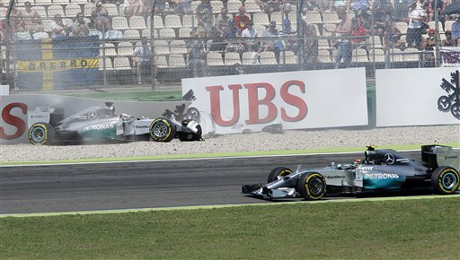 Mercedes driver Lewis Hamilton of Britain has crashed as Mercedes driver Nico Rosberg of Germany drives by during the qualifying of the German Formula One Grand Prix in Hockenheim, Germany, Saturday, July 19, 2014. The German Grand Prix will be held on Sunday. (AP Photo/Michael Probst)