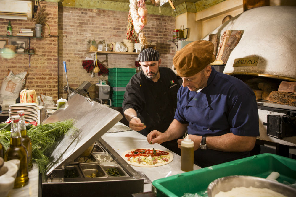 Chef de cuisine Giancarlo Dellanzo and chef/restaurateur Nicola Accardi putting finishing touches on a pizza before putting it in the oven. Behind them, the double-chambered wood oven. (Edward Dai/Epoch Times)