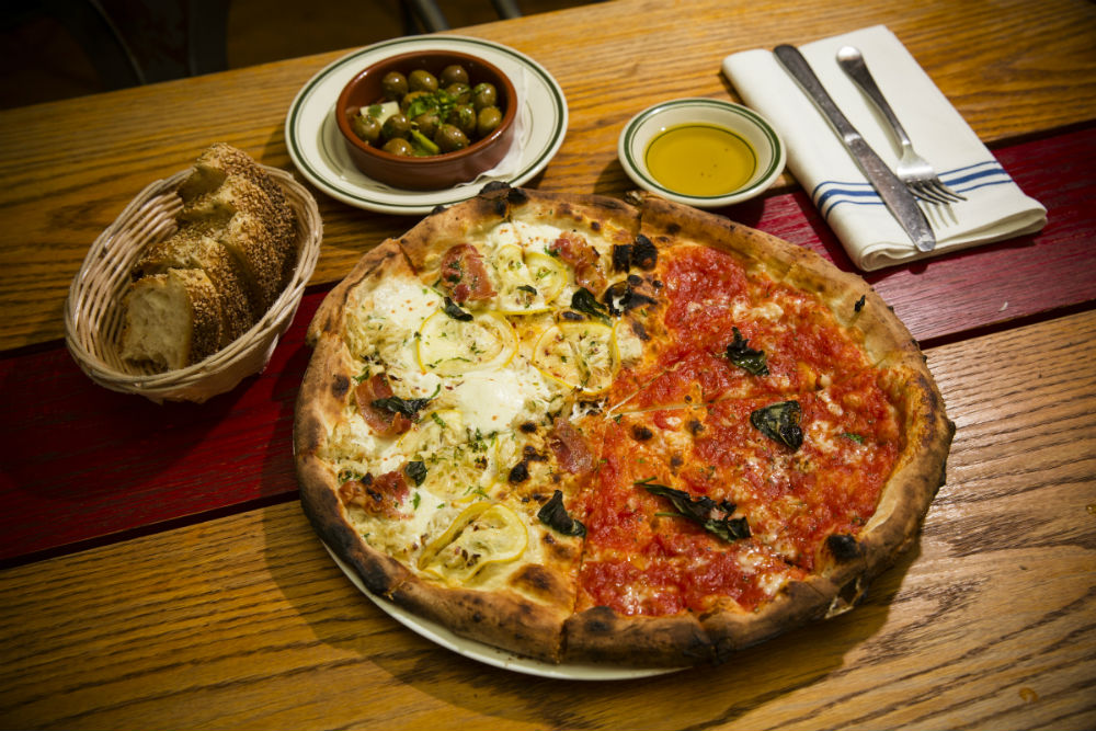 The pizzas are crispy, light, flavorful. Above, half margherita and half pancetta, clams, and lemons. (Edward Dai/Epoch Times)